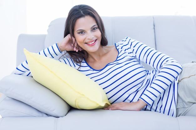 Lächelnder schöner brunette, der auf der couch sich entspannt und kamera betrachtet
