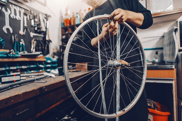 Lächelnder schöner kaukasischer mann, der fahrradrad in den händen hält, während in werkstatt steht.