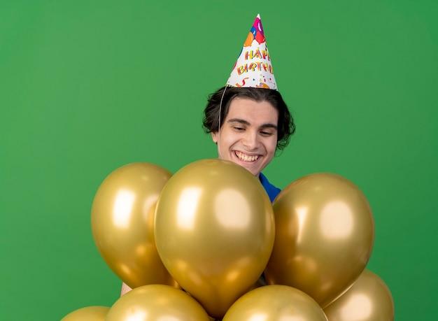 Lächelnder schöner mann, der geburtstagskappe trägt, schaut und steht mit heliumballons lokalisiert auf grüner wand
