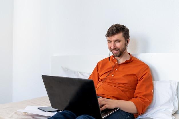 Lächelnder schöner mann, der laptop zu hause benutzt