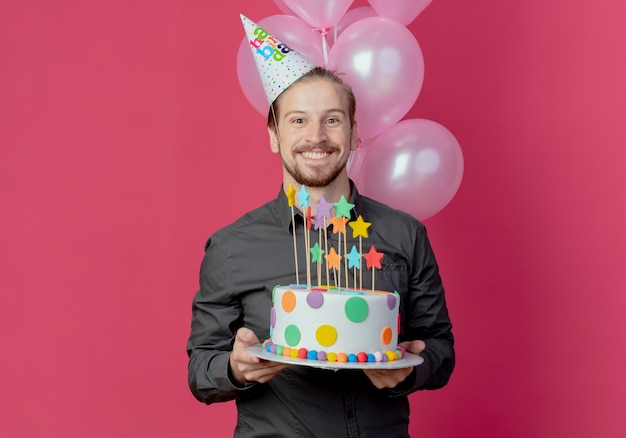 Lächelnder schöner mann in der geburtstagskappe steht mit heliumballons, die geburtstagstorte halten