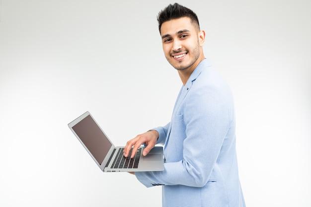 Lächelnder schöner mann in einer blauen jacke mit einem offenen laptop in seinen händen auf einem weißen studiohintergrund