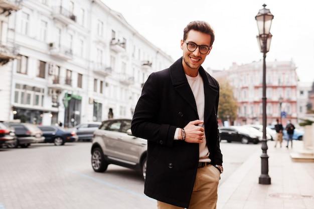 Lächelnder schöner schöner mann in der jacke, die auf der straße aufwirft. männliche herbstmodetrends.