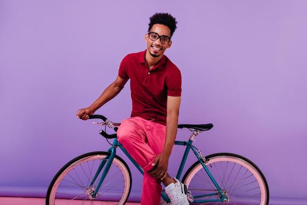 Lächelnder schüchterner afrikanischer kerl in der rosa hose, die mit fahrrad aufwirft. hübscher schwarzer mann isoliert.