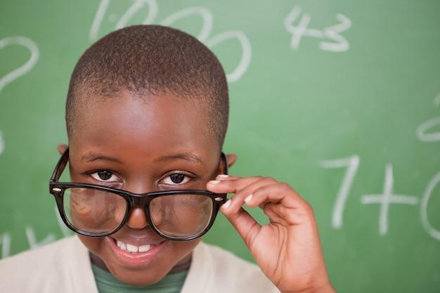 Lächelnder schüler, der über seinen gläsern schaut