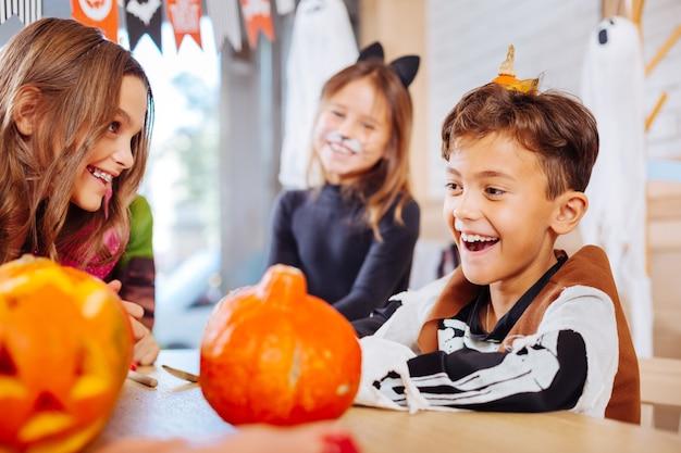 Lächelnder schüler. hübscher lächelnder schuljunge, der sich erstaunlich fühlt, während er skelettkostüm für halloween-partei trägt