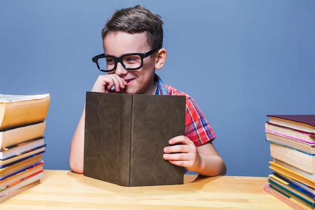 Lächelnder schüler in gläsern mit buch, das an der schulbank sitzt. wissen aus einem lehrbuch holen