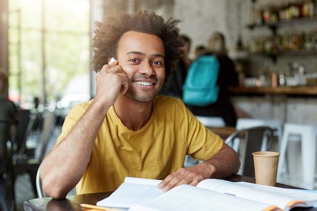 Lächelnder schwarzer junge, der in der cafeteria sitzt und über smartphone spricht, das breites lächeln und gute laune hat, während er ruhe hat