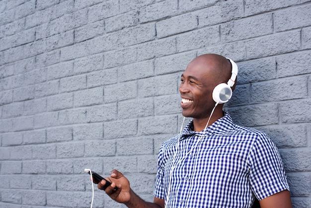 Lächelnder schwarzer kerl mit kopfhörern und handy