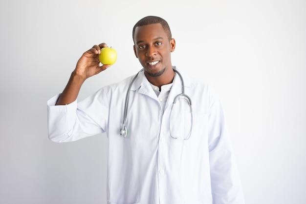 Lächelnder schwarzer männlicher doktor, der apfel zeigt und empfiehlt.