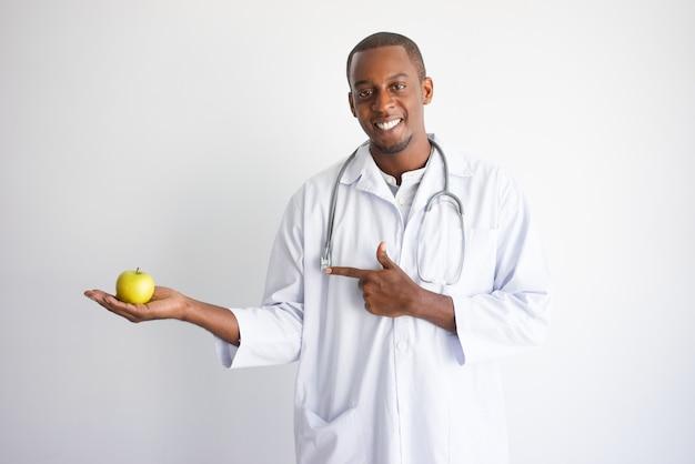 Lächelnder schwarzer männlicher doktor, der auf apfel hält und zeigt.
