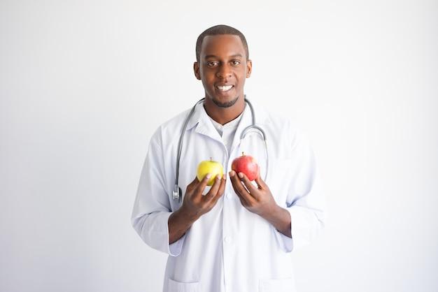 Lächelnder schwarzer männlicher doktor, der gelben und roten apfel hält.