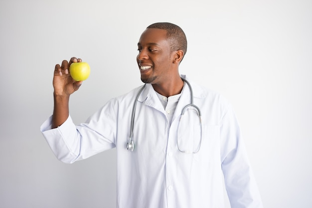 Lächelnder schwarzer männlicher doktor, der grünen apfel hält.