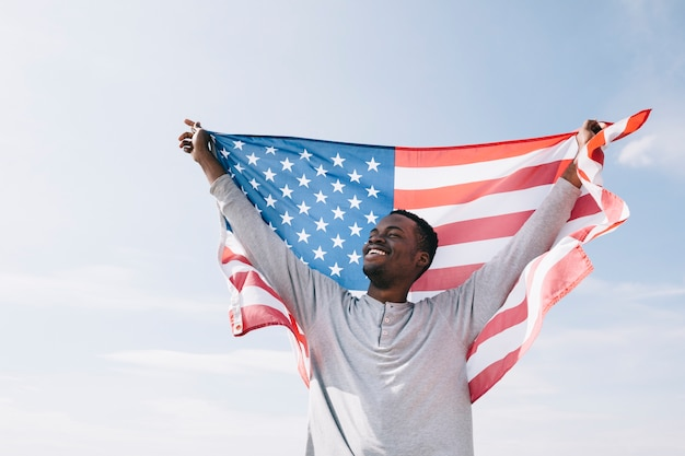 Lächelnder schwarzer mann, der wellenartig bewegende flagge hält