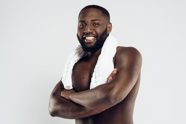 Lächelnder schwarzer mann mit nacktem oberkörper hält handtuch.