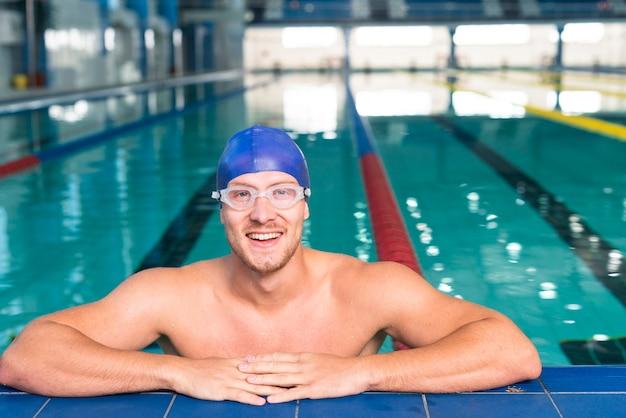 Lächelnder schwimmer, der auf rand des pools stationiert