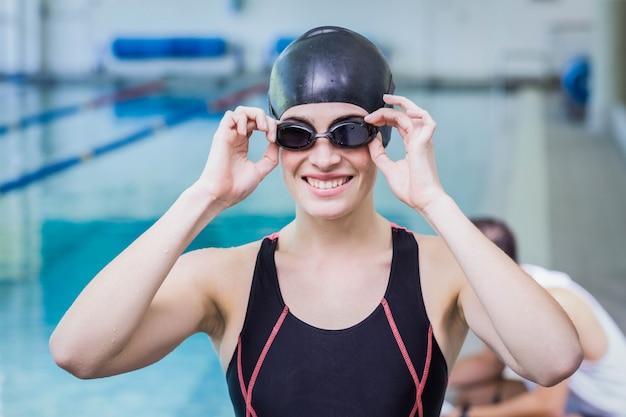 Lächelnder schwimmer, der die kamera in der freizeitmitte betrachtet