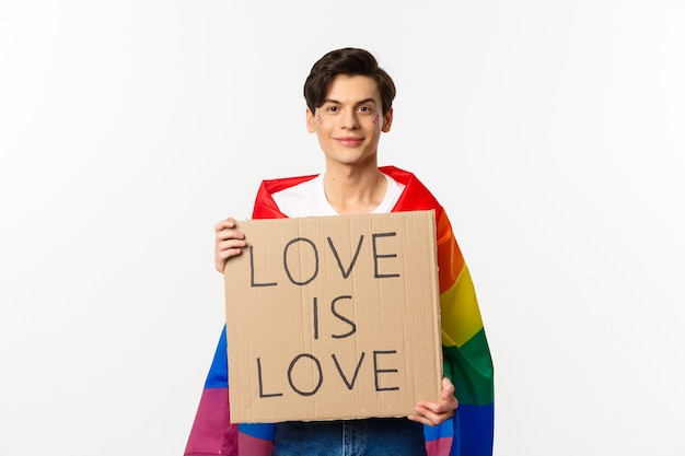 Lächelnder schwuler mannaktivist, der zeichenliebe hält, ist liebe für lgbt stolzparade, regenbogenfahne tragend, über weiß stehend. speicherplatz kopieren