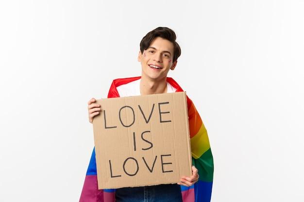 Lächelnder schwuler mannaktivist, der zeichenliebe hält, ist liebe für lgbt stolzparade, regenbogenfahne tragend, über weiß stehend.