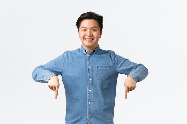 Lächelnder selbstbewusster asiatischer mann, der mit seiner stomatologie-klinik zufrieden ist, arzt empfehlen, stolze zahnspangen zeigen, mit den fingern zufrieden nach unten zeigend, weißer hintergrund stehen