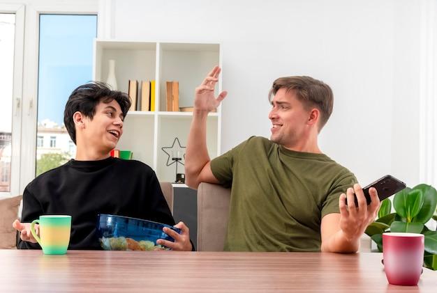 Lächelnder selbstbewusster junger blonder gutaussehender mann hält telefon und hebt hand, die am tisch sitzt