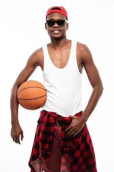 Lächelnder selbstbewusster junger mann, der basketballball steht und hält