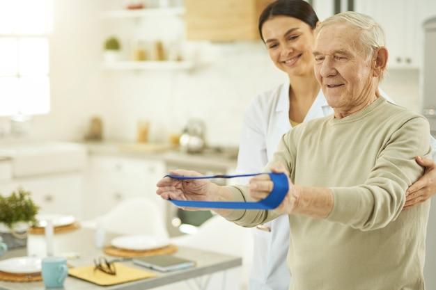 Lächelnder senior mit fitness-gummiband in den händen während der rehabilitation