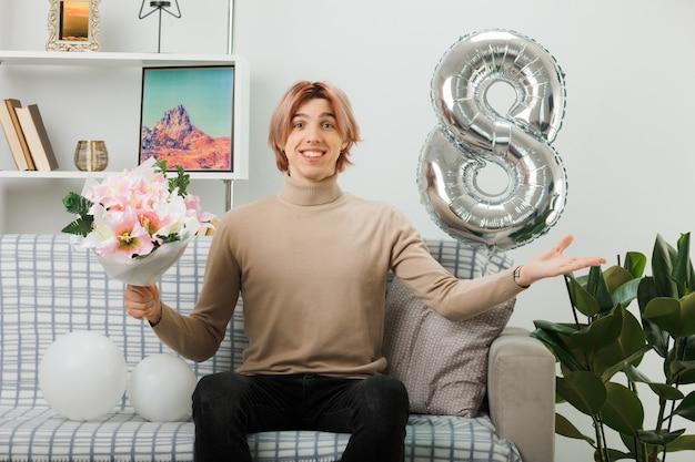 Lächelnder, sich ausbreitender, gutaussehender kerl am glücklichen frauentag, der einen blumenstrauß auf dem sofa im wohnzimmer hält