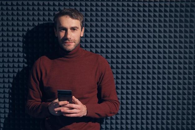 Lächelnder sicherer mann, der smartphone über grauem hintergrund mit geometrischen formen und lichtspiel hält.