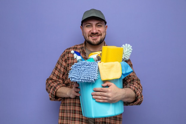 Lächelnder slawischer putzmann, der reinigungsgeräte hält