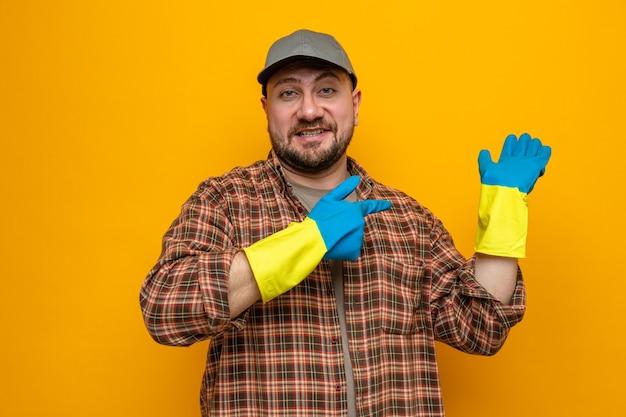 Lächelnder slawischer putzmann mit gummihandschuhen, die auf seine leere hand zeigen