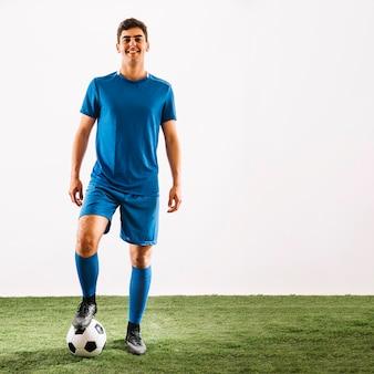Lächelnder sportler, der auf ball tritt