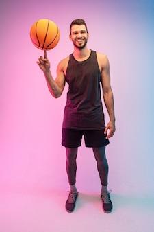 Lächelnder sportler, der basketballball auf finger spinnt. vorderansicht des jungen bärtigen europäischen basketballspielers, der kamera betrachtet. getrennt auf blauem und rosa hintergrund. studioshooting