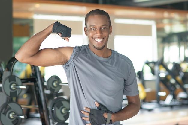 Lächelnder sportlicher schwarzer mann, der bizeps in der turnhalle zeigt