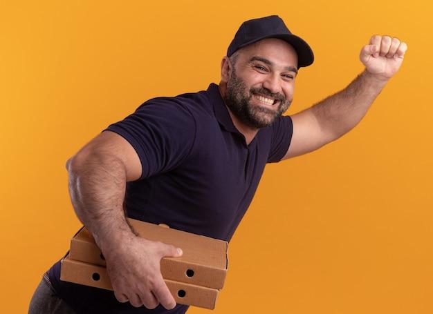 Lächelnder stehender in der profilansicht lieferbote mittleren alters in uniform und mütze, die pizzaschachteln hält und laufgeste lokalisiert auf gelber wand zeigt