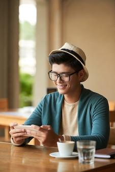 Lächelnder stilvoller asiatischer mann, der im café sitzt und mitteilungen auf smartphone überprüft