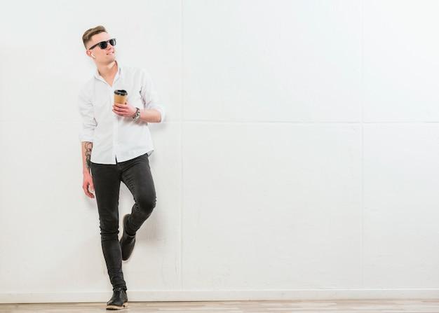 Lächelnder stilvoller junger mann, der die wegwerfkaffeetasse zum mitnehmen steht gegen weiße wand hält