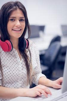 Lächelnder student, der an computer an der universität arbeitet