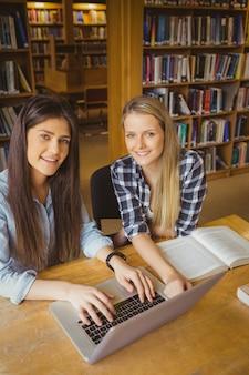 Lächelnder student, der an der bibliothek an der universität arbeitet