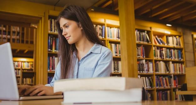 Lächelnder student, der an laptop in der bibliothek arbeitet