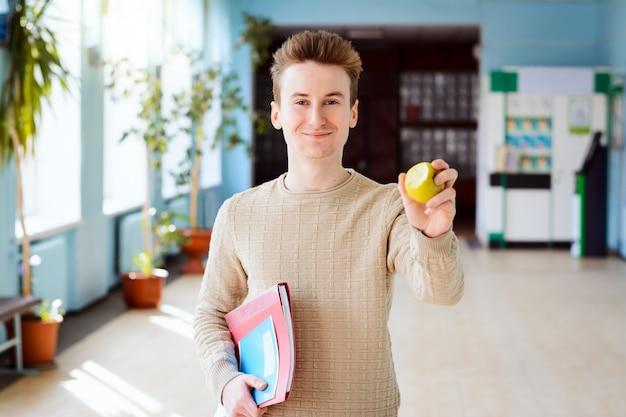 Lächelnder student, der einen apfel isst, der im universitätskorridor steht