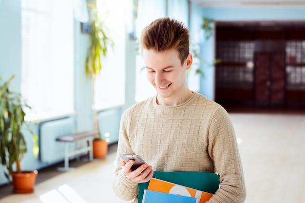 Lächelnder student, der sein telefon durchsucht, bücher hält und in die klasse geht