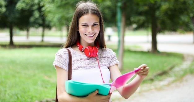 Lächelnder student im freien, der ein buch liest
