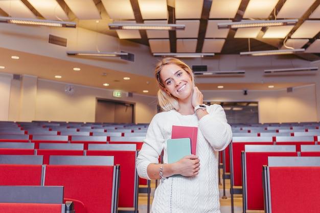 Lächelnder student mit notizbüchern in der halle