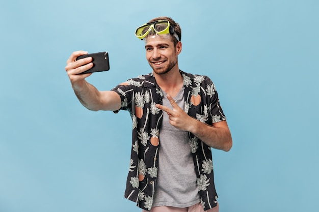 Lächelnder stylischer bärtiger mann in schwarzem sommerhemd und cooler grüner schwimmbrille macht foto, zeigt friedenszeichen und lächelt