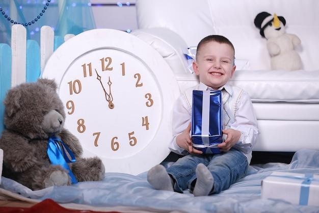 Lächelnder süßer junge, der sein geschenk während der weihnachtszeit hält. große weiße uhr und teddybär an der wand