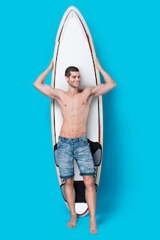 Lächelnder surfer, der ein surfbrett hält
