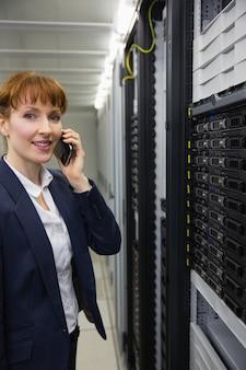 Lächelnder techniker, der am telefon beim betrachten des servers spricht
