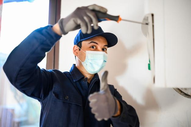 Lächelnder techniker, der einen warmwasserbereiter mit maske repariert, coronavirus-konzept