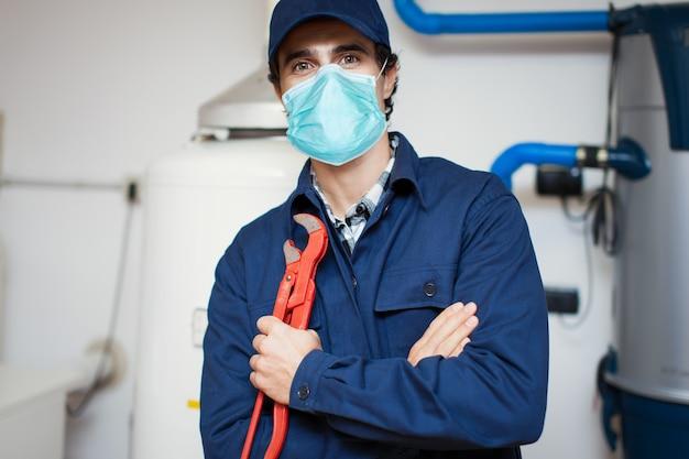 Lächelnder techniker, der einen warmwasserbereiter repariert, der eine maske trägt, coronavirus-konzept